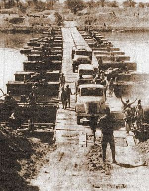 Egyptian military trucks cross a bridge laid over the Suez Canal on October 7, 1973.